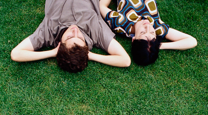 two student lying on lawn looking up