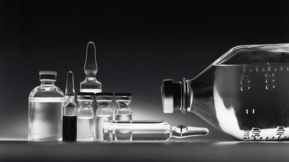 Chemotherapy drugs in vials and bottles against a black background