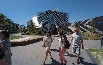 Group of students walking outside New Horizons building, Monash University