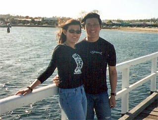 Image of a man and woman with the beach in the background
