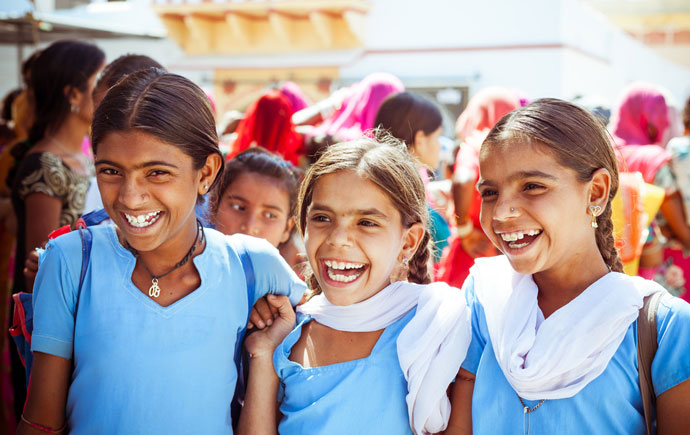 Group of happy indian school girls wearing blue school uniforms posing in the rural village