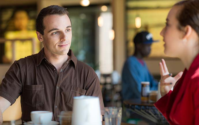 Male listening to female student in cafe