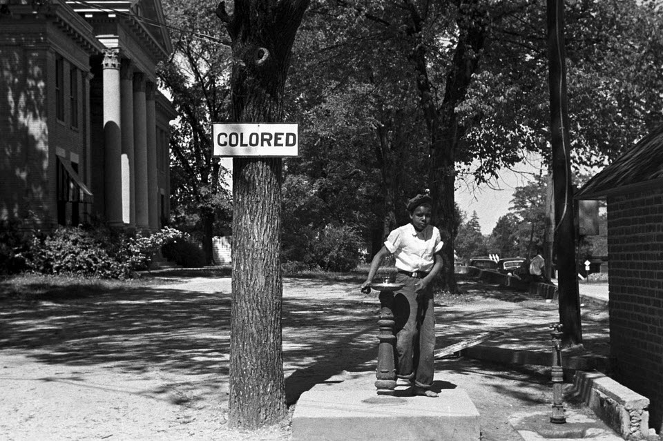 small boy next to sign saying 'coloured'