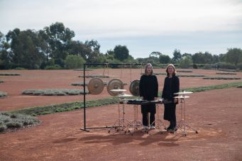 This image shows two women standing in a dessert surrounded by musical instruments.