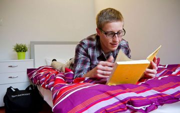 Student reading book on bed