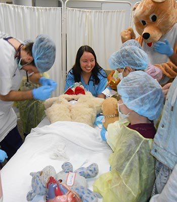 Students with children at a teddy bear hospital