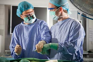Surgeon wearing magnifying glasses demonstrates use of surgical instrument to a student, both wearing surgical scrubs