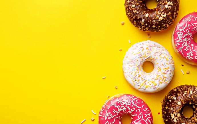 Flat lay donuts on a yellow background