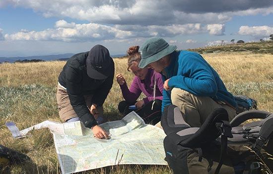 3 people reading a map in an open field