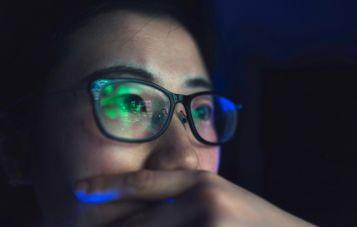 Woman looking at the screen at night