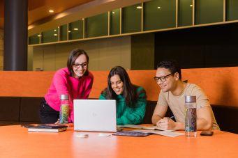 Three people around computer