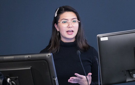 A Monash Master of Strategic Communications Management student is standing behind two computer screens and a lectern, presenting to a group. She is wearing round clear-rimmed glasses and her hands are gesturing at an important point.