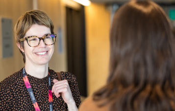 A Monash School of Film, Media and Journalism Masters staff member is smiling and talking to a student. She is wearing a dotted patterned shirt and her hair is short.