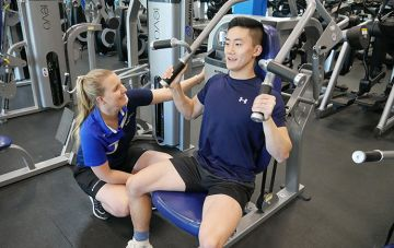 Trainer helps gym user on machine
