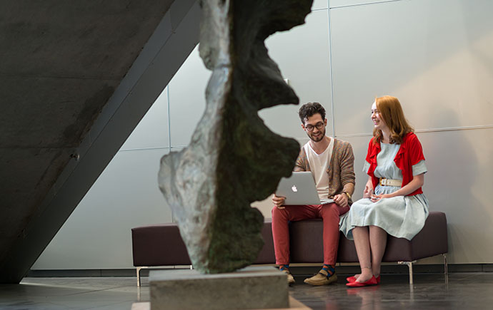 Students sitting with laptop in foyer