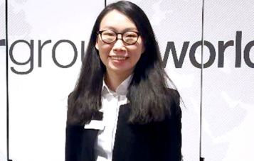 Monash Master of Communications and Media Studies alumni Rachel Yao is standing in front of a corporate sign and smiling at the camera. She has long dark hair and is wearing thick black rimmed glasses.