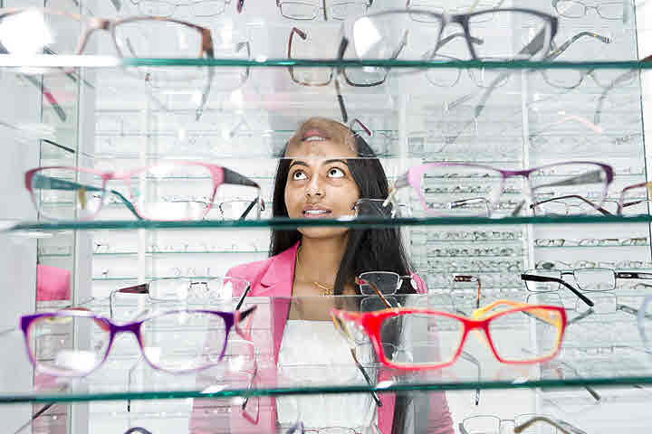 Lady looking at glasses on a shelf