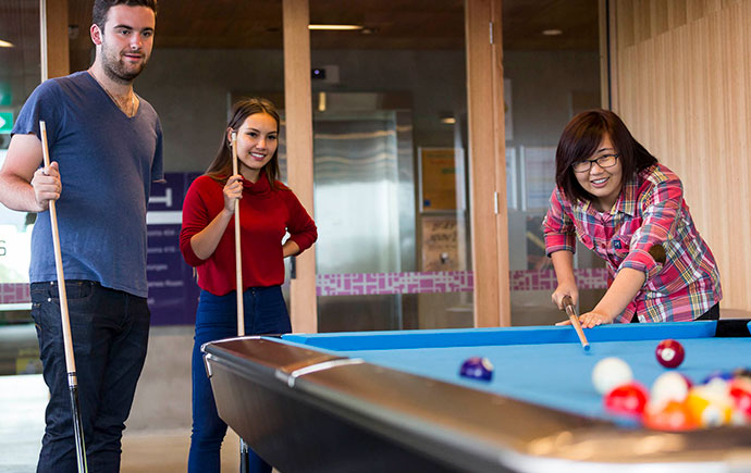 Students waiting their turn at the pool table
