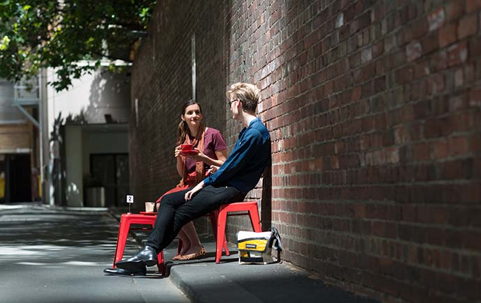 Female and male student enjoying coffee by brick wall