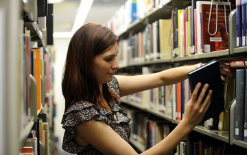 Student return book on library shelf