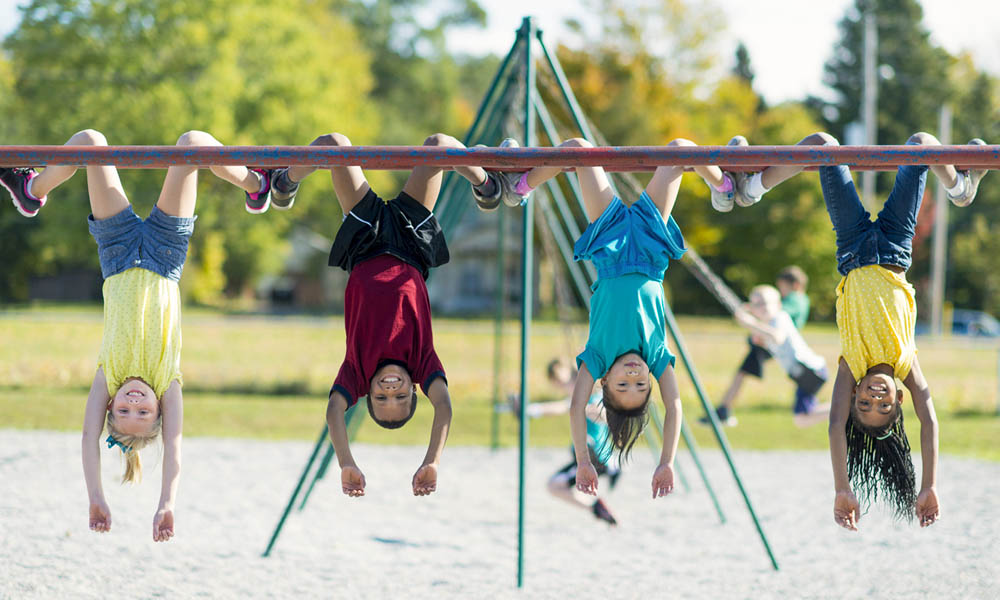 Children hanging on monkey bars in a playground