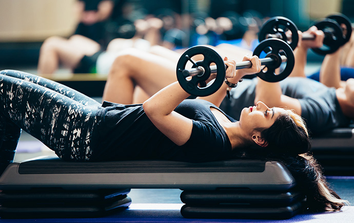 Fitness class student bench pressing