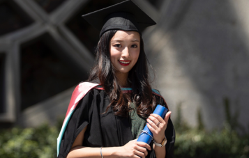 Monash Master of Communications and Media Studies alumni Olivia OuYnag stands in front of a building and garden in her graduation gown and cap, smiling at the camera.