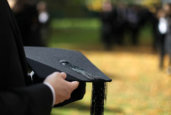 Graduate holding a mortarboard