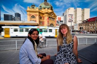 Two people sitting outside Flinders Street Station, Victoria
