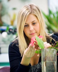 Student examining a flower