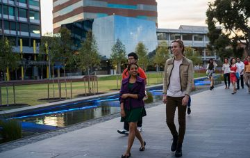 Students walk by Caufield water feature