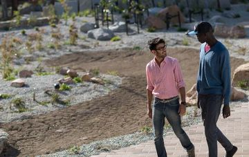 Two male students walking by landscaping