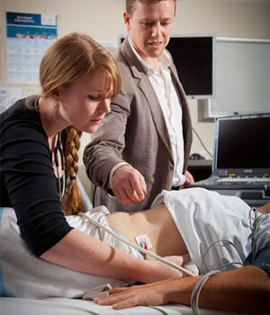 Female student examines abdomen of female patient who is lying on examination table with ultrasound, while specialist observes