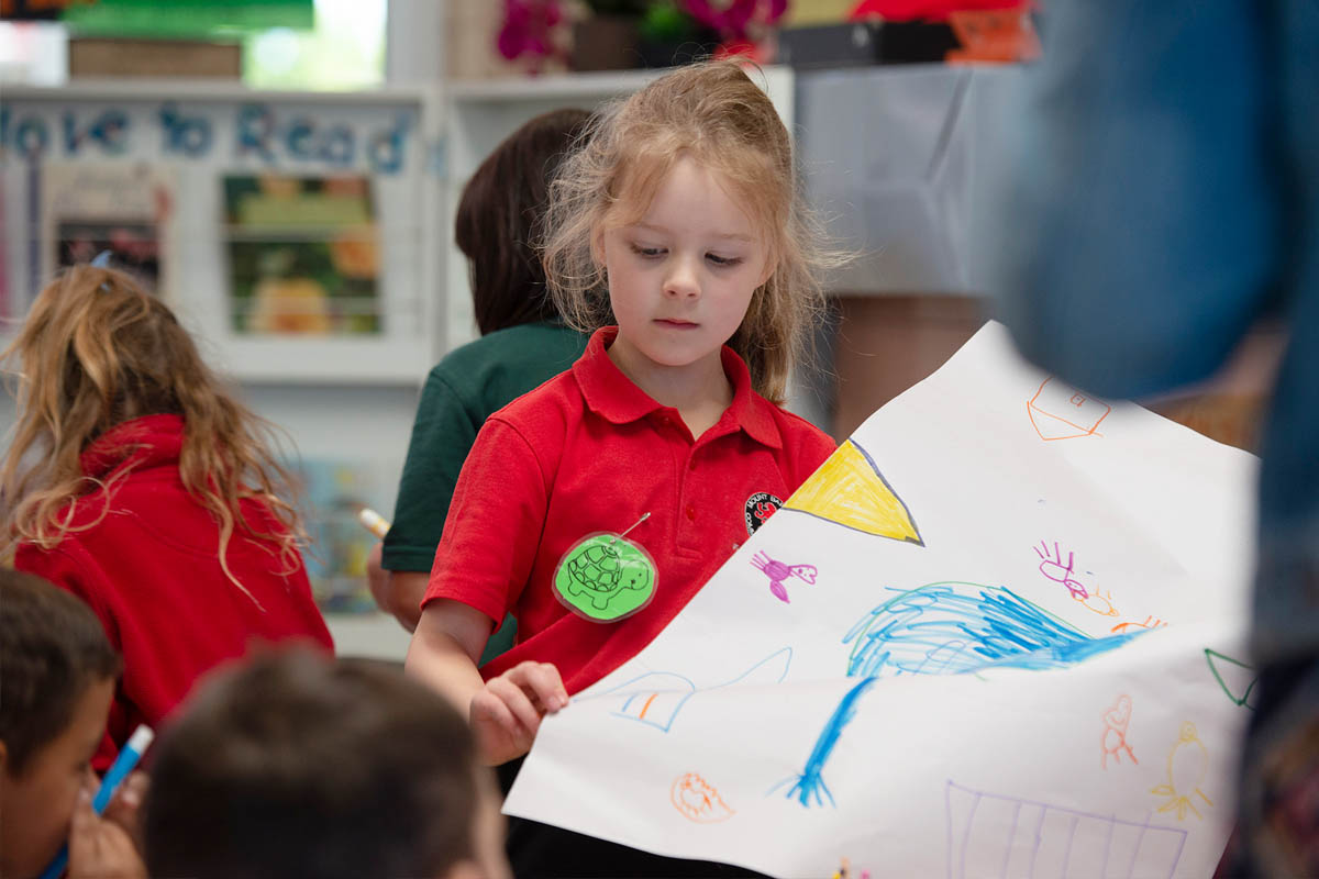 A child shows off her drawing