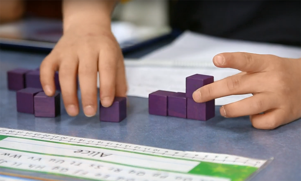 child's hands building with purple cubes