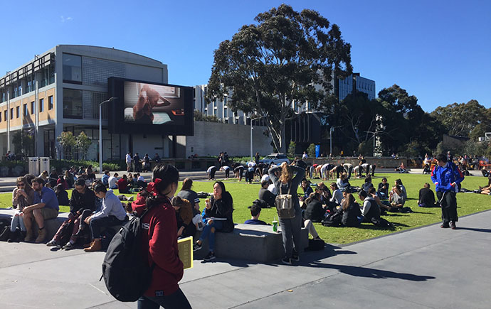 Students relax by Northern Plaza screen