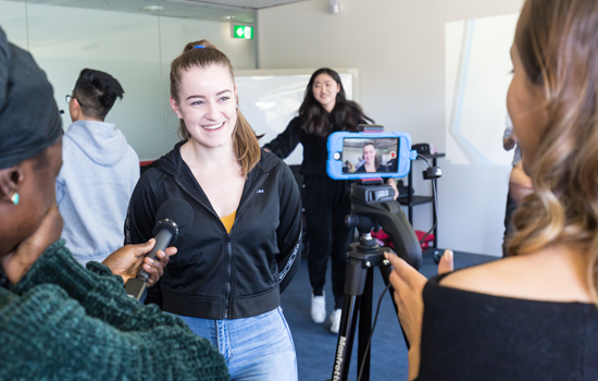 Monash Master of Journalism students are practicing filmed interviews. A young woman stands smiling at a camera on a tripod. In the foreground a microphone is being held out towards the young woman.