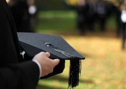 Graduate holding a mortarboard (graduation hat)