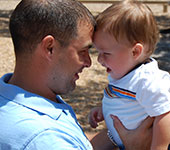 Father holding baby at a playground