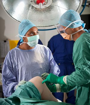Male surgeon with female student examining patient's knee in surgical theatre