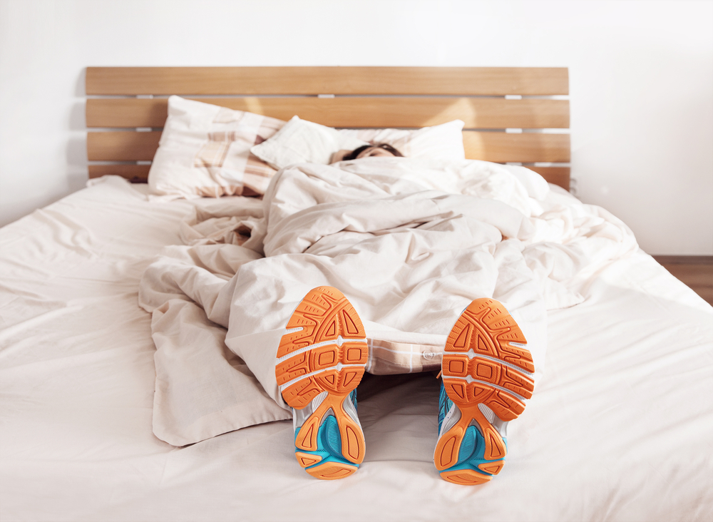 Person sleeping with runners on their feet