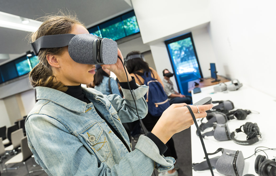 A group of Monash Master of Communication and Media Studies students are gathered in a room. In the foreground is a young man and woman. The woman is wearing a VR headset and a denim jacket.