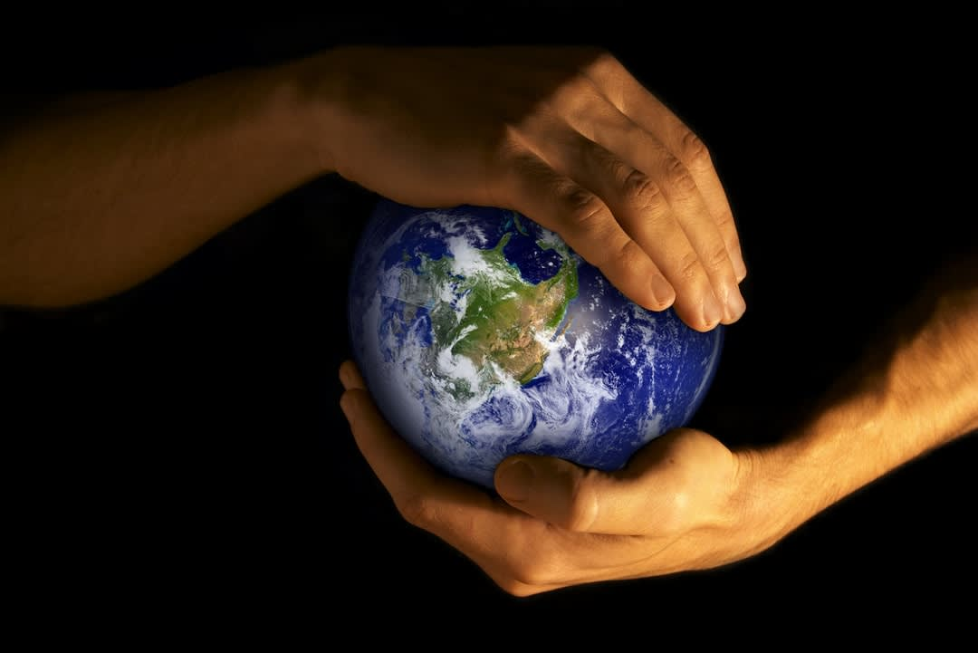 Depiction of planet Earth being cradled in human hands