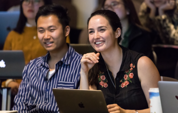 A man and woman, both Masters students at Monash School of Film, Media and Journalism happily smile towards the camera and a lecturer out of the shot. They're leaning forward, engaged and with their laptops open. More students sit behind them in the auditorium.
