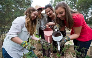 Female students watering plants together