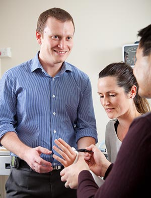 Two consultants examining a patient's wrist