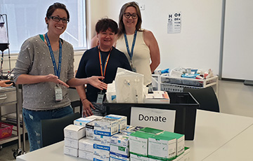 Three educators with donated supplies