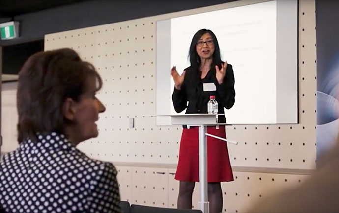 Woman Giving a Presentation at Front of Room