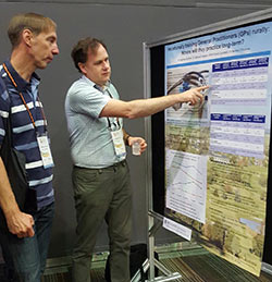 Matthew McGrail explains his poster to a male conference delegate