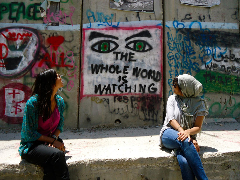 Graffiti in Israel, 'the whole world is watching'.